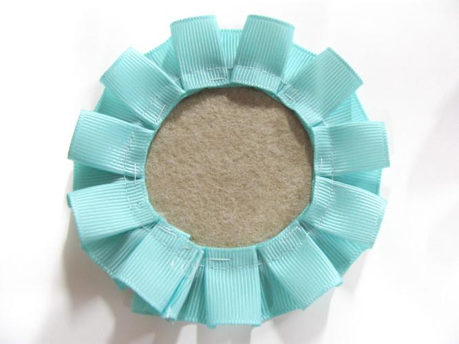大きい円をフェルトに縫付けます。 Sew the bigger circle on the felt.