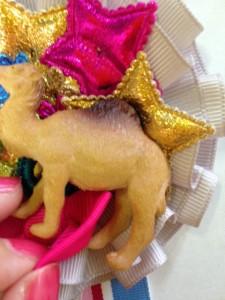 リボンをラクダの後足の間に はさみます。 Put the bow between camel's hind legs.